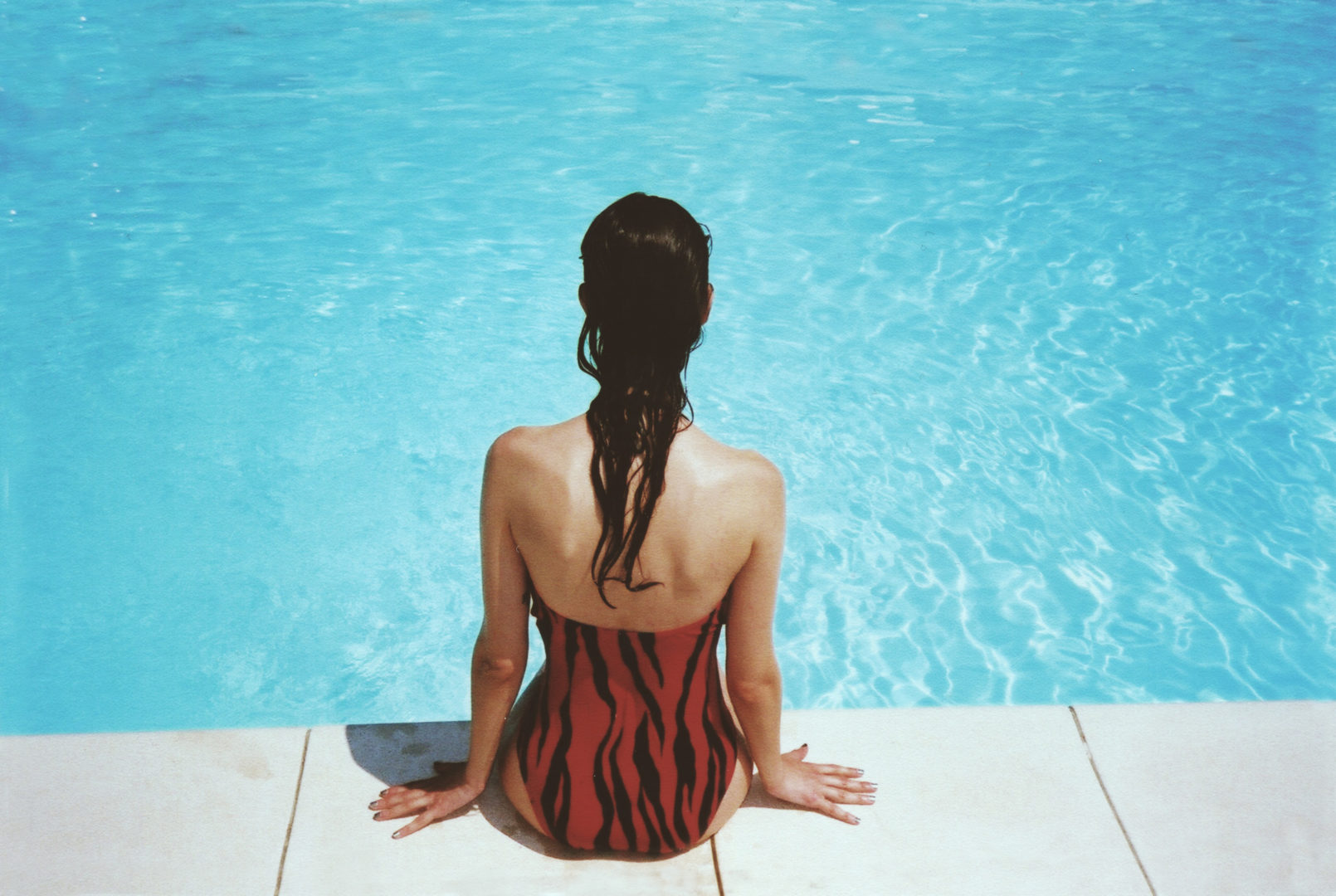 Woman sitting beside the pool